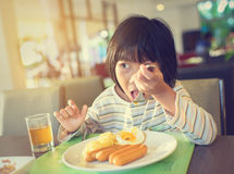 Ασιατικό κορίτσι που τρώει το πρόγευμα με τις πυτζάμες Στοκ Φωτογραφίες