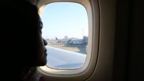 Ασιατικό κορίτσι που φαίνεται μέσω του παραθύρου ο αερολιμένας από το αεροπλάνο φιλμ μικρού μήκους