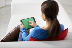 Ασιατικό κορίτσι που χρησιμοποιεί τη συσκευή μαξιλαριών αφής Στοκ εικόνα με δικαίωμα ελεύθερης χρήσης