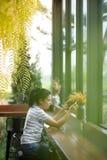 Ασιατικό κορίτσι φωτογραφιών που χρησιμοποιεί την κινητή τηλεφωνική φωτογραφία ενώ σε μια καφετερία Στοκ Εικόνες
