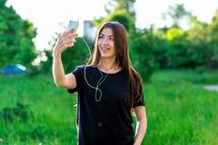 Ασιατικό κορίτσι Brunette το καλοκαίρι στο πάρκο Ευτυχή στηρίγματα δοντιών χαμόγελου Κρατά το τηλέφωνο στο τηλέφωνο ακούοντας τη  Στοκ φωτογραφίες με δικαίωμα ελεύθερης χρήσης