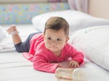 Ασιατικό κοριτσάκι που σέρνεται στο άσπρο κρεβάτι Στοκ Φωτογραφίες