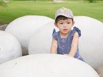Ασιατικό κοριτσάκι σχετικά με ένα αυγό δεινοσαύρων για να εξερευνήσει εάν αισθάνεται τίποτα μέσα στοκ εικόνα