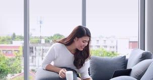Ασιατικό κύπελλο καφέ εκμετάλλευσης γυναικών και χρησιμοποίηση του lap-top απόθεμα βίντεο