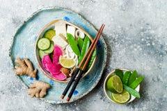 Ασιατικό κύπελλο σούπας νουντλς udon Vegan με την πιπερόριζα και το ζωμό μανιταριών, tofu, τα αιφνιδιαστικά μπιζέλια, τα κολοκύθι Στοκ Φωτογραφία