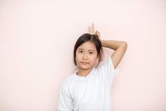 Ασιατικό μαυρισμένο πορτρέτο παιδιών κοριτσιών δερμάτων πέρα από το ρόδινο υπόβαθρο τοίχων στοκ φωτογραφία με δικαίωμα ελεύθερης χρήσης