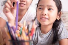 Ασιατικό μικρό κορίτσι και μια γυναίκα που επιλέγει ένα χρώμα για τη ζωγραφική στοκ εικόνα