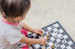 Ασιατικό μικρό κορίτσι με το παιχνίδι σκακιού στο σπίτι Στοκ εικόνα με δικαίωμα ελεύθερης χρήσης