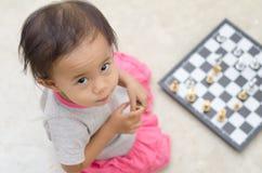 Ασιατικό μικρό κορίτσι με το παιχνίδι σκακιού στο σπίτι Στοκ Φωτογραφίες