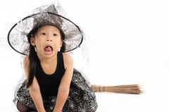 Ασιατικό μικρό κορίτσι πορτρέτου που ντύνει στη χαριτωμένη μάγισσα για αποκριές στοκ εικόνα