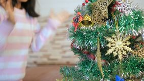 Ασιατικό μικρό κορίτσι που διακοσμεί ένα χριστουγεννιάτικο δέντρο και που προσεύχεται για το καλύτερο thingHappy ασιατικό μικρό κ απόθεμα βίντεο