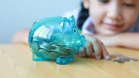 Ασιατικό μικρό κορίτσι στο ταϊλανδικό παιδικών σταθμών νόμισμα χρημάτων τοποθέτησης σπουδαστών ομοιόμορφο στη σαφή piggy τράπεζα  φιλμ μικρού μήκους