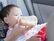 Ασιατικό μικρό παιδί που τρώει το μπουκάλι του γάλακτος και που κάθεται στο αυτοκίνητο Στοκ Εικόνες