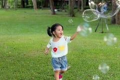 Ασιατικό μπαλόνι φυσαλίδων παιχνιδιού κοριτσάκι χαμόγελου στοκ φωτογραφίες