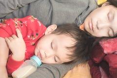 Ασιατικό μωρό εκμετάλλευσης μητέρων στο βραχίονα ενώ πόσιμο γάλα μωρών από το μπουκάλι στοκ φωτογραφία
