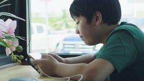 Ασιατικό νέο αγόρι που απολαμβάνει το παιχνίδι στο μαξιλάρι αφής στον καφέ φιλμ μικρού μήκους