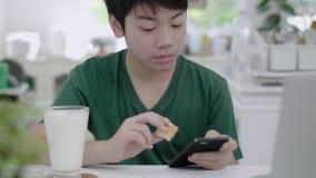 Ασιατικό νέο αγόρι που χρησιμοποιεί τους κυλίνδρους μέσω των εφαρμογών smartphone, ενώ αργά τρώει το οργανικό πρόγευμα γάλακτος απόθεμα βίντεο