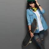 Ασιατικό νέο κορίτσι σκέιτερ που κρατά skateboard Στοκ εικόνα με δικαίωμα ελεύθερης χρήσης