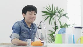 Ασιατικό νέο πιάτο πλύσης αγοριών στην κουζίνα στο σπίτι, έννοια τρόπου ζωής φιλμ μικρού μήκους