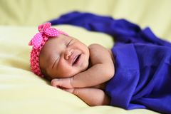 Ασιατικό νεογέννητο μωρό στο κίτρινο υπόβαθρο που τυλίγεται με το μπλε ύφασμα Στοκ εικόνες με δικαίωμα ελεύθερης χρήσης