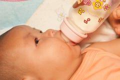 Ασιατικό νεογέννητο πόσιμο γάλα μωρών από το μπουκάλι στοκ εικόνες με δικαίωμα ελεύθερης χρήσης