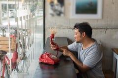 Ασιατικό ντροπαλό περιμένοντας τηλεφώνημα ατόμων σε μια καφετερία στοκ εικόνες