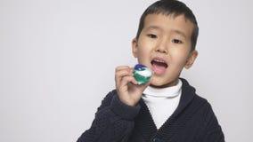 Ασιατικό παιδί που προσπαθεί να φάει το λοβό σκονών πλύσης Πρόκληση λοβών σκονών πλύσης, Διαδίκτυο meme 60 fps φιλμ μικρού μήκους