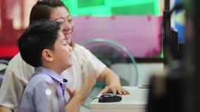 Ασιατικό παιδί που εξετάζει τον υπολογιστή στη βιβλιοθήκη με το δάσκαλό τους στο δημοτικό σχολείο φιλμ μικρού μήκους
