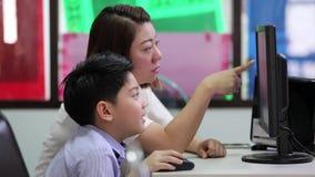 Ασιατικό παιδί που εξετάζει τον υπολογιστή στη βιβλιοθήκη με το δάσκαλό τους στο δημοτικό σχολείο απόθεμα βίντεο