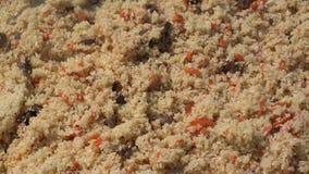 Ασιατικό παραδοσιακό μαγειρικό πιάτο - pilaf Μαγειρεύοντας pilaf, αναμιγνύοντας pilaf το κουτάλι κουζινών εκμετάλλευσης στο καζάν απόθεμα βίντεο