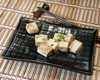 Ασιατικό πιάτο tofu με τα scallions σε ένα μπαμπού placemat με τα κοντινά ραβδιά μπριζολών στοκ εικόνα με δικαίωμα ελεύθερης χρήσης