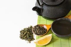 Ασιατικό πράσινο τσάι που τίθεται στο χαλί μπαμπού με το ξηρό πράσινο τσάι στο κουτάλι Ασιατική έννοια τσαγιού Στοκ Εικόνες