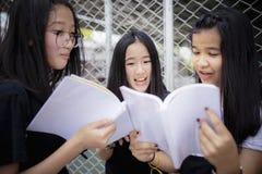 Ασιατικό σχολικό βιβλίο εκμετάλλευσης εφήβων και γέλιο με τη συγκίνηση ευτυχίας που στέκεται υπαίθρια στοκ φωτογραφίες
