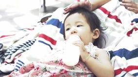Ασιατικό ταΐζοντας μωρό μητέρων ένα μπουκάλι του γάλακτος στο σπίτι με το πρόσωπο χαμόγελου, ευτυχής ασιατική οικογενειακή έννοια απόθεμα βίντεο