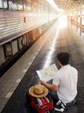 Ασιατικό ταξιδιωτικό άτομο με τις περιουσίες που περιμένει το ταξίδι με το τραίνο Στοκ Φωτογραφίες