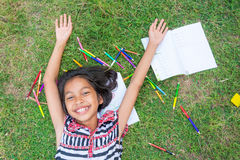 Ασιατικό ταϊλανδικό κορίτσι που βρίσκεται στη χλόη με το χρωματισμένο μολύβι και homew Στοκ φωτογραφία με δικαίωμα ελεύθερης χρήσης