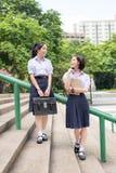Ασιατικό ταϊλανδικό υψηλό ζεύγος σπουδαστών μαθητριών στη στάση σχολικών στολών στοκ εικόνες