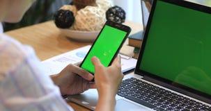 Ασιατικό τηλέφωνο κυττάρων εκμετάλλευσης χεριών γυναικών Τηλέφωνο και lap-top στο γραφείο με την πράσινη οθόνη απόθεμα βίντεο