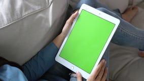 Ασιατικό χέρι εκμετάλλευσης γυναικών και προσοχή χρησιμοποιώντας τον υπολογιστή ταμπλετών με την πράσινη οθόνη για το περιεχόμενο φιλμ μικρού μήκους