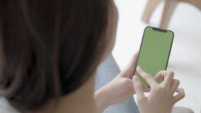 Ασιατικό χέρι εκμετάλλευσης γυναικών και προσοχή χρησιμοποιώντας το έξυπνο κινητό τηλέφωνο με την πράσινη οθόνη για το περιεχόμεν απόθεμα βίντεο