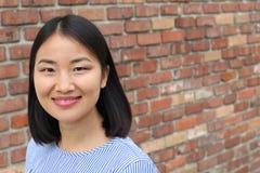 Ασιατικό χαμόγελο γυναικών που απομονώνεται στο τουβλότοιχο με το διάστημα για το αντίγραφο Στοκ Εικόνες