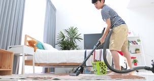Ασιατικό χαριτωμένο αγόρι που κάνει τα οικιακά μανικών, την οικοκυρική, και την οικιακή έννοιά σας φιλμ μικρού μήκους