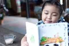 Ασιατικό χαριτωμένο πόσιμο γάλα κοριτσιών και διαβασμένο βιβλίο στη καφετερία Στοκ Εικόνες