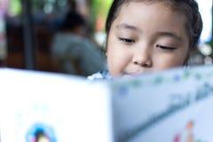 Ασιατικό χαριτωμένο πόσιμο γάλα κοριτσιών και διαβασμένο βιβλίο στη καφετερία Στοκ Φωτογραφία