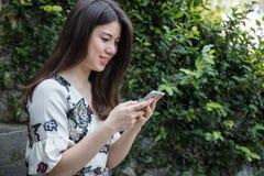 Ασιατικό όμορφο νέο παιχνίδι γυναικών με το έξυπνο τηλέφωνο στοκ εικόνες με δικαίωμα ελεύθερης χρήσης