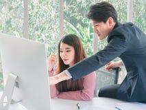 Ασιατικό όμορφο νέο σημείο επιχειρηματιών στο όργανο ελέγχου οθόνης στοκ εικόνα