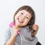 Ασιατικό όμορφο τραγούδι μικρών κοριτσιών με το μικρόφωνο, ασιατικό μικρό κορίτσι, μικρό παιδί Στοκ Φωτογραφία