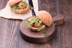 Ασιατικό burger με τις γαρίδες, το arugula, την ντομάτα και το κρεμμύδι με την άσπρη σάλτσα Στοκ φωτογραφία με δικαίωμα ελεύθερης χρήσης