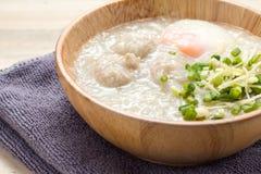 Ασιατικό congee με το κομματιασμένο χοιρινό κρέας και αυγό στο άσπρο κύπελλο Στοκ Εικόνες