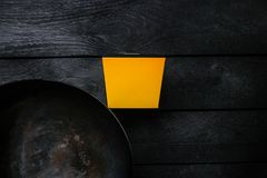Ασιατικό Wok - παραδοσιακό ασιατικό τηγάνι σε ένα μαύρο ξύλινο υπόβαθρο Με ένα κιβώτιο για τα νουντλς Τοπ όψη Στοκ φωτογραφία με δικαίωμα ελεύθερης χρήσης